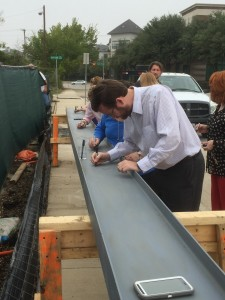 Board President and Hope Cottage adoptee, John Dickey signs the beam